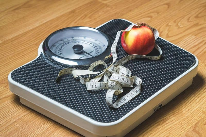 scale with apple and tape measure for weight measurement