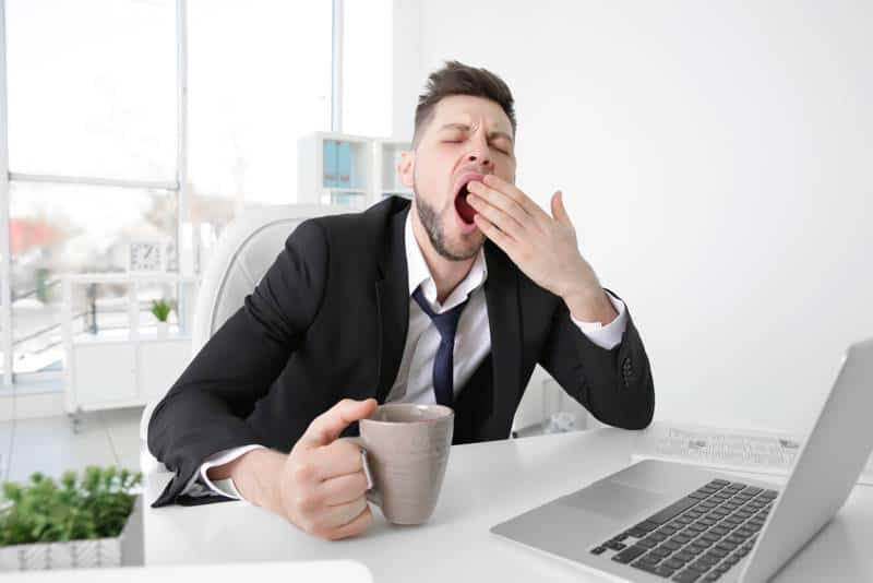 man yawning at desk - does cbd oil make you tired