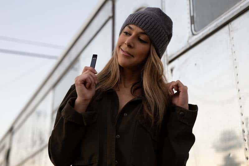 young woman vaping cbd with battery powered vape pen