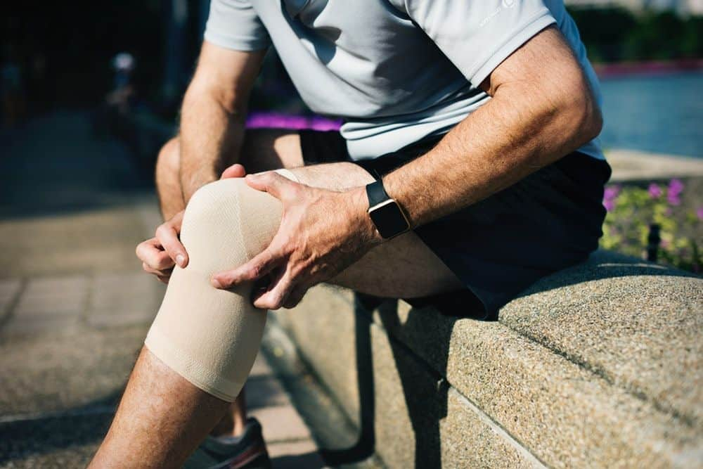cbd relieves pain - man on bench with knee brace