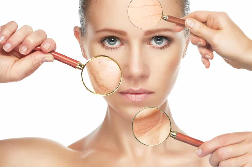hemp oil has anti-aging properties - woman with youthful skin and magnifying glasses highlighting different areas of her face