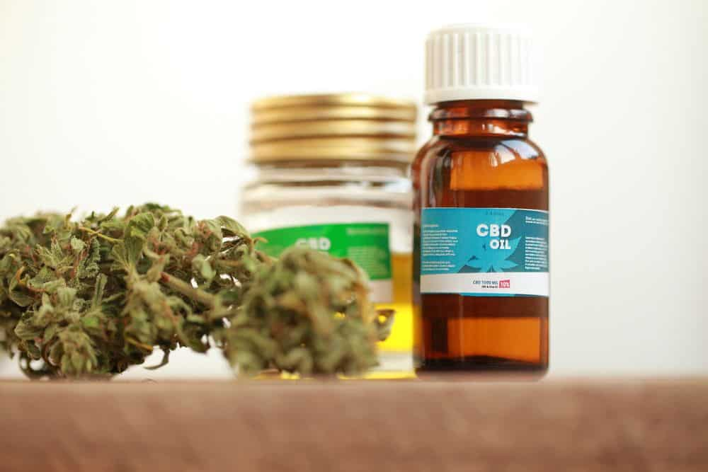 how does cbd oil make you feel - image of cbd oil bottles next to cannabis flower